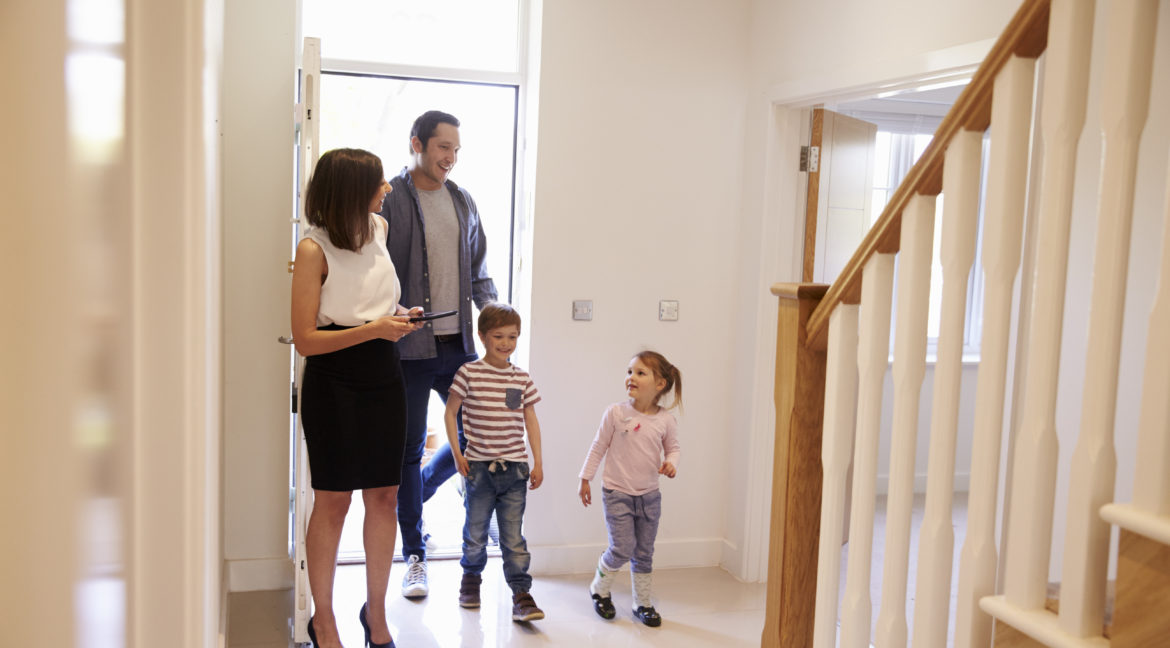 Realtor Showing Young Family Around Property Listing